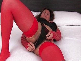 Mature in stockings works her hairy pussy