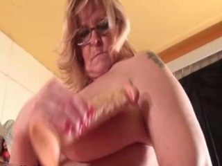 Curvy granny puts pokes her pussy with a dildo